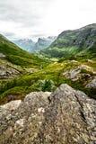 在绿色牧场地的道路西挪威山的有雪的在山顶和黑暗的多云天空 库存照片