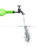 在绿色瓶的龙头与水和泡影 图库摄影