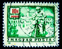 在绿色的匈牙利打印的邮票显示骑一辆经典摩托车的一个人的图象在价值在10 Ft 库存照片