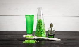 在绿色的绿色构成秀丽治疗产品:香波,肥皂,腌制槽用食盐,油 免版税库存图片