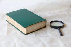 在绿色盖子和放大镜的旧书 免版税库存照片