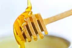 在绿色碗的倾吐的金黄甜蜂蜜陶瓷与木h 免版税库存图片