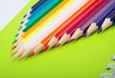 在绿色笔记本的颜色铅笔 库存图片
