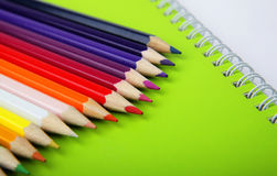 在绿色笔记本的颜色铅笔 免版税库存照片
