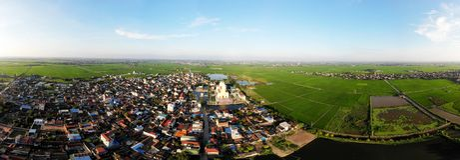 在绿色米领域之间的美丽的村庄 免版税库存照片