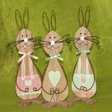 在绿色背景前面的三只木复活节兔子 库存照片