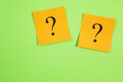 在绿色背景的二个橙色问号 免版税图库摄影
