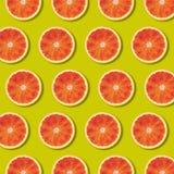 在绿色背景的几何红色橙色果子切片样式 库存照片