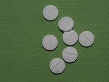 在绿色背景的各种各样的药片 库存照片