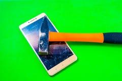 在绿色背景的锤子捣毁的智能手机 库存图片