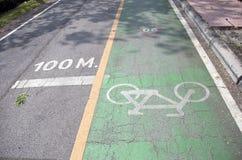 在绿色自行车车道的白色自行车绘画在100米线距离 库存照片