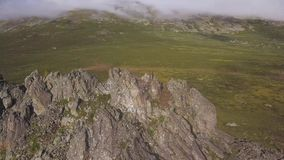 在绿色草甸的鸟瞰图有偏僻的岩石和多云天空背景 惊人的山环境美化与大岩石在 影视素材