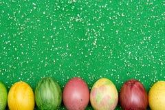 在绿色透明硬沙织品背景的五颜六色的复活节彩蛋 怂恿手工制造新式着色 样式,复活节概念 图库摄影