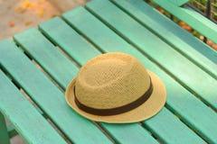 在绿色长木凳的帽子在公园 免版税库存照片