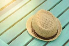 在绿色长木凳的帽子在公园 库存照片