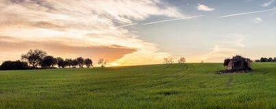 在绿色领域的小屋在与云彩的日落在天空 库存图片