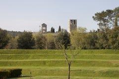在绿色领域的步与修道院在背景中 免版税库存照片