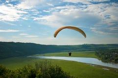 在绿色领域的滑翔伞在夏天晴天 在绿色领域的一次滑翔伞飞行在Dnister河附近在乌克兰 库存照片