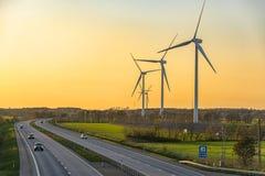 在绿色领域的风力场发电器的图片接近有汽车的路在日落 免版税库存图片