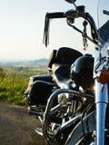 在绿色风景的站立的摩托车 免版税库存照片