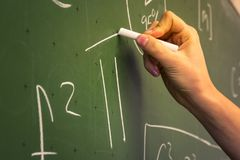 在绿色黑板教授Univer的女性手老师文字 免版税图库摄影