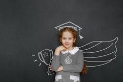 在绿色黑板附近的聪明的卷曲女孩在教室 库存图片