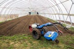 在绿色hous里面的BCS 853普遍的拖拉机单位运作的土壤土 库存照片