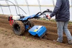 在绿色hous里面的BCS 853普遍的拖拉机单位运作的土壤土 免版税图库摄影