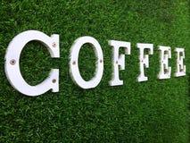 在绿草墙壁上的白色木咖啡文本 免版税库存照片
