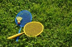 在绿草的二副羽毛球球拍 免版税库存照片