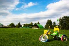 在绿草的五颜六色的玩具儿童的自行车 免版税库存图片