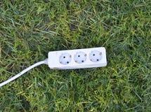 在绿草的电多个插口 绿色能量概念 库存图片
