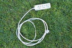 在绿草的电多个插口 绿色能量概念 库存照片