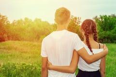 在绿草的美好的年轻夫妇与在面孔的微笑,愉快的关系 图库摄影