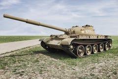 在绿草的老坦克在蓝天下 免版税库存图片