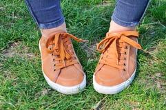 在绿草的运动鞋 免版税库存照片