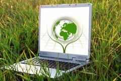 在绿草的银色膝上型计算机。 生态概念 免版税库存图片