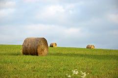 在绿草的领域的圆的干草捆与蓝天和云彩的 免版税库存照片