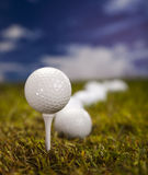 在绿草的高尔夫球在蓝天 免版税图库摄影