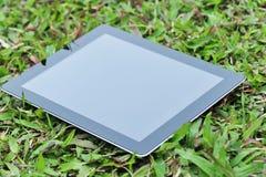 在绿草的黑色ipad 库存图片