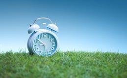 在绿草,白色背景的逗人喜爱的蓝色闹钟 免版税库存照片