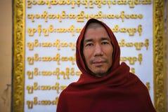 在缅甸文字前面的修士姿势 免版税库存图片