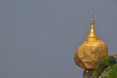 在缅甸的普遍的金黄岩石与灰色天空(空间)在左边可以由设计师使用为消息 库存图片