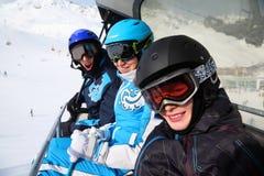在缆索铁路的三个滑雪者乘驾在山 库存图片