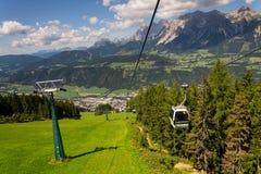 在缆车的游客旅行对Planai自行车和滑雪地区2017年8月15日在施拉德明,奥地利 免版税库存照片