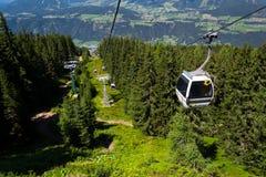 在缆车的游客旅行对Planai自行车和滑雪地区2017年8月15日在施拉德明,奥地利 图库摄影