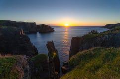 在缆绳约翰小海湾纽芬兰的剧烈的日出峭壁 在大西洋的破晓 免版税图库摄影