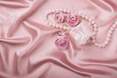 在缎背景的一个礼物盒用花和珍珠装饰 平的布局 库存图片