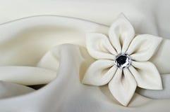 在缎背景的手工制造丝织物花 库存照片