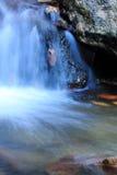 在缎软的河溪包围的岩石的抽象美丽的景色 库存照片
